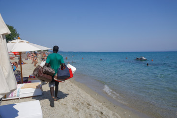 Vendor with counterfeit products on the beach in Chaniotis, Greece. Street vendor selling popular brands replicas bags by a Greek beach shore on a sunny summer day.