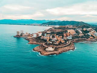 Beautiful mediterranian coastline near Valencia, Spain with small town, hotels, buildings and roads. Autumn winter blue turquoise cold sea water and warm colors coastline. Aerial drone shot view Fototapete