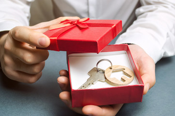 Man holds a miniature house in a gift box. Housing as a gift. Win an apartment in the lottery. To inherit property. Holiday discounts. Buying an apartment at a low price. Sale of real estate. Present