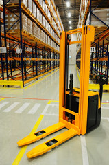 Yellow forklift in warehouse, industrial storage racking in background