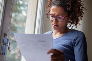 Portrait of worried black woman standing beside window
