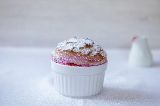 Raspberry souffle in a white ramekin