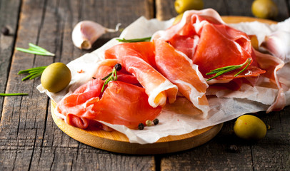 Closeup of thin slices of prosciutto with mixed olives and paprika on wooden cutting board