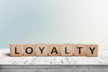 Loyalty sign on a wooden table in bright daylight