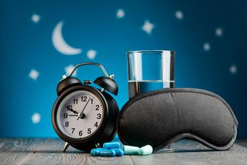 Clock, pills, earplugs, mask
