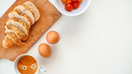 Pyszne i zdrowe śniadanie. Jajka, pocięta bułka, pomidorki i kawa