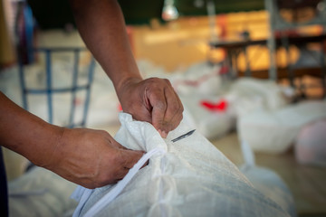 Thai workers sew sacks by hand.