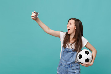 Surprised young girl football fan with soccer ball doing selfie shot on mobile phone isolated on blue turquoise background. People emotions, sport family leisure lifestyle concept. Mock up copy space.