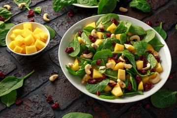 Mango Spinach salad with dried cranberries and nuts. healthy food.