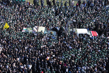 Iranian people along with members of Iran's elite Revolutionary Guards gather around the coffins of Iran's elite Revolutionary Guards, who were killed by a suicide car bomb, during the funerals in Isfahan