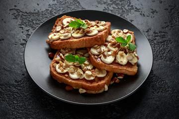 French cinnamon toast with banana, nuts and hazelnut, honey.