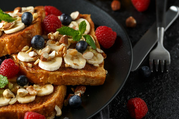 French cinnamon toast with blueberries, raspberries, banana, nuts, hazelnut and honey.