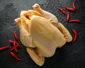 Raw whole chicken with spices on dark background