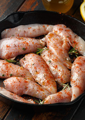 Raw chicken breast mini fillets in rastic cast iron skillet, frying pan with herbs and sea salt