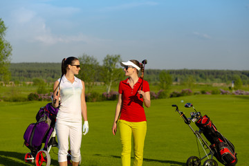Two pretty women golfers walking at golf course