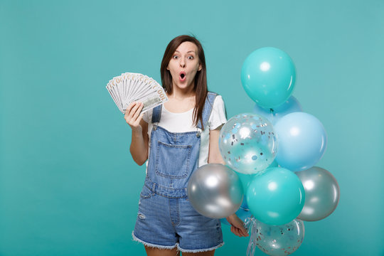 Amazed young woman holding fan of money in dollar banknotes cash money, celebrating with colorful air balloons isolated on blue turquoise background. Birthday holiday party, people emotions concept.