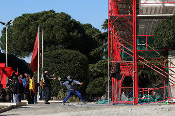 A supporter of the opposition party hurls stones during an anti-government protest in front of the office of Albanian Prime Minister Edi Rama in Tirana