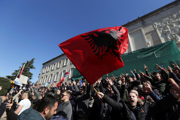 Supporters of the opposition party wave Albanian flags during an anti-government protest in front of the office of Albanian Prime Minister Edi Rama in Tirana