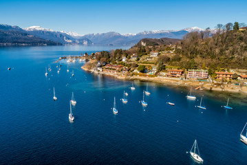 Aerial view of Lake Maggiore with boats in the harbor of Monvalle village, province of Varese, Italy Wall mural