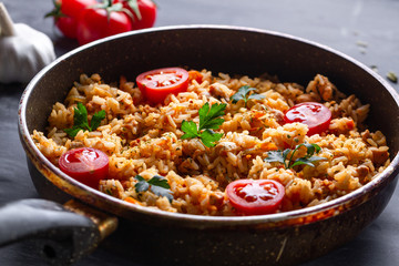 Homemade delicious pilaf with chicken, fresh parsley and ripe vegetables in a pan for lunch on a dark background