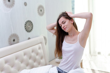 Sleepy smiling young woman with long hair with closed eyes trying to waking up early in the morning for start new day