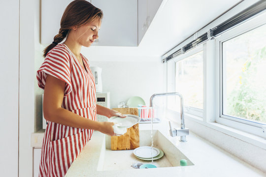 Teenage girl washing dishes in the kitchen