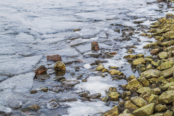 Morning on the river bank.Side view close up on an river shore of small pebbles, and with washed up green stones.
