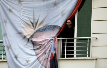A supporter of Turkish President Tayyip Erdogan looks out of a window during a rally for the upcoming local elections in Istanbul