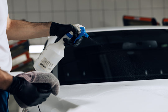 hardworking guy cleaning car windshield with cloth and spray bottle, close up cropped photo. business