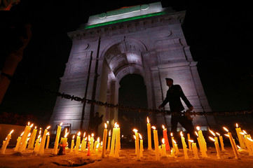 A soldier walks during a candle light vigil to pay tribute to CRPF personnel who were killed after a suicide bomber rammed a car into the bus carrying them in south Kashmir on Thursday, in front of India Gate war memorial in New Delhi
