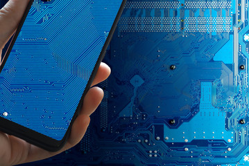 A hand with a smartphone photographs a technological electronic circuit. Industrial espionage. Mobile espionage.