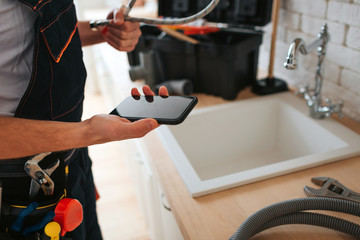 Cut view of man standing in kitchen at sink. He hold phone and wrench. Hose on desk.