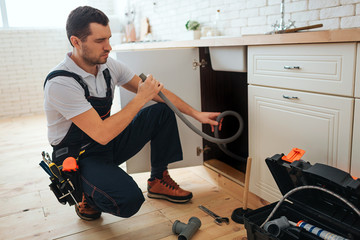 Concentrated young worker doing repairing in kitchen. He sit in squad pose and hold hose. Piece of pipe on floor. Opened toolbox.