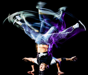 one chinese young man hip hop break dancer dancing isolated on black background with speed light painting effect motion blur