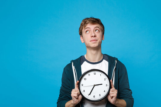 Portrait of pensive young man in casual clothes looking up, holding round clock isolated on blue wall background. Time is running out. People sincere emotions, lifestyle concept. Mock up copy space.