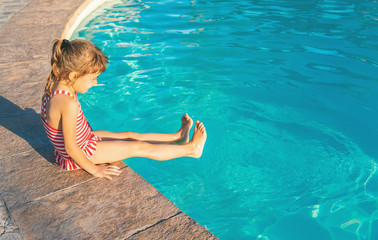 A child swims in a swimming pool with a life preserver. Selective focus.
