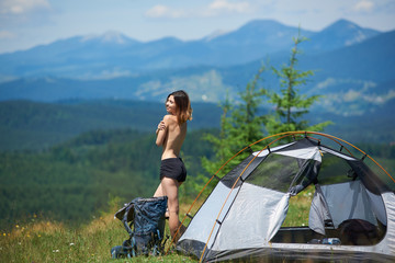 Side view of attractive naked female tourist standing near the tent and backpack, enjoying summer morning in the mountains. Camping lifestyle concept adventure vacations outdoor Wall mural