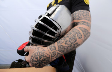 A competitor of Buhurt Prime holds his helmet before the tournament of medieval martial fights in real armors and steel swords in Monaco