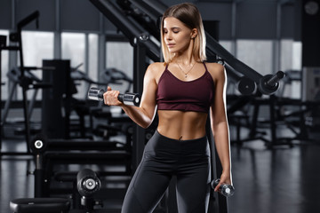 Sexy athletic girl working out in gym. Fitness woman doing exercise for biceps