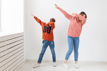 Fun, mothers day, children and family concept - teen boy and his mom funny dancing on white...