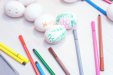 Easter eggs with children's drawings are on the table with markers. Easter ideas. Space for text. Happy easter.Toned image.