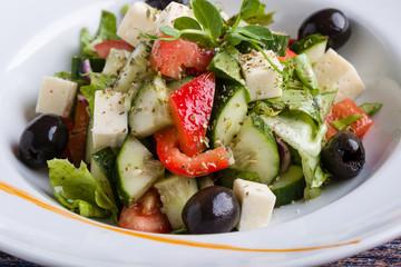 fresh tasty greek salad appetizer on white plate