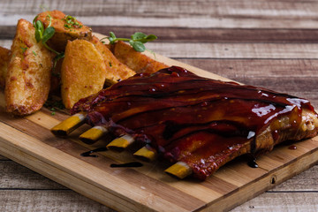 grilled pork ribs with potato on wooden table