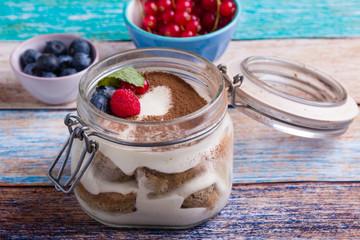 tasty tiramisu dessert in glass jar on color table