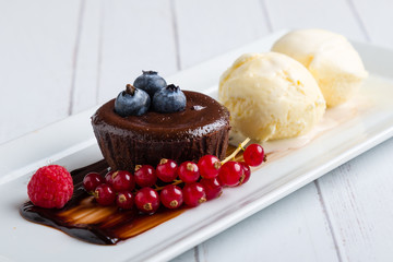 lava cake with ice cream and fruits on white plate