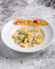 chicken with mushrooms sauce and polenta cubes in white table