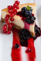 fresh tasty cheese cake with fruits on white plate
