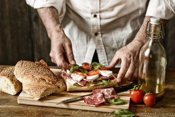 prepare a sandwich with Italian ham, mozzarella and tomato - eat healthy and traditional - desaturated effect - selective focus