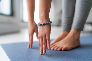 Yoga at home exercise in living room house - woman on fitness mat training stretching legs touching toes.