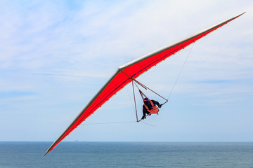 Hang gliding man flying on an orange wing at Fort Funston in San Francisco, one of the premier hang-gliding spots in the country Wall mural